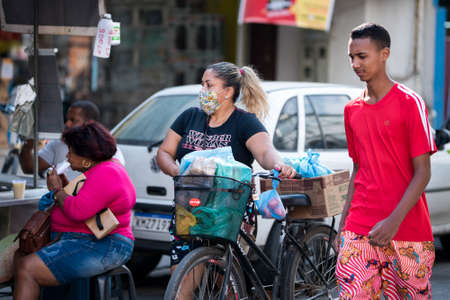 Rio de Janeiro, Brazil - July 3, 2020: Only some people are wearing face masks during the Coronavirus pandemic in suburban area of the city. Woman walking her bicycle with shopping bags. Редакционное