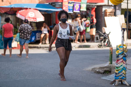 Rio de Janeiro, Brazil - July 3, 2020: People are wearing face masks during the Coronavirus pandemic in suburban area of the city. Woman with headphones crossing the street.
