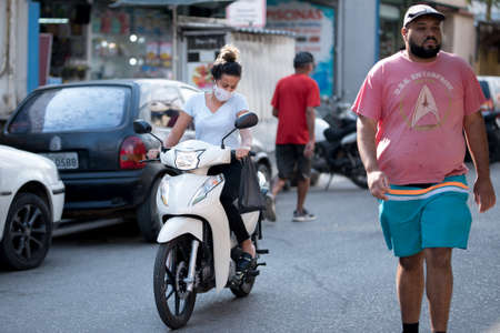 Rio de Janeiro, Brazil - July 3, 2020: Only some people are wearing face masks during the Coronavirus pandemic in suburban area of the city. Woman on a scooter in the street.