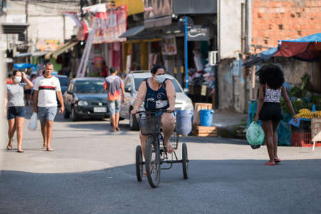 Rio de Janeiro, Brazil - July 3, 2020: People are wearing face masks during the Coronavirus pandemic in suburban area of the city. Woman on a tricycle among other people in the street.