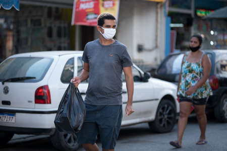 Rio de Janeiro, Brazil - July 3, 2020: People are wearing face masks during the Coronavirus pandemic in suburban area of the city. Man carrying black plastic bag.