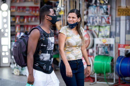 Rio de Janeiro, Brazil - July 3, 2020: People are wearing face masks during the Coronavirus pandemic in suburban area of the city. Man and woman walking ant talking.