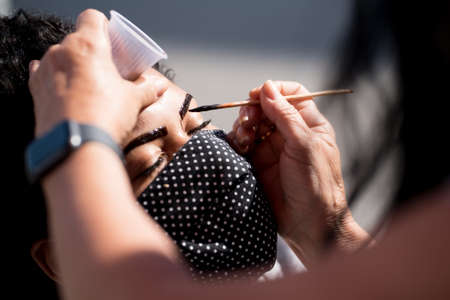 Rio de Janeiro, Brazil - July 3, 2020: Young woman in protective mask is having a procedure of micro pigmentation for eyebrows.