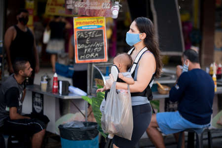 Rio de Janeiro, Brazil - July 3, 2020: People are wearing face masks during the Coronavirus pandemic in suburban area of the city. Mother carrying her baby and shopping bags.