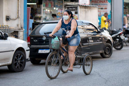 Rio de Janeiro, Brazil - July 3, 2020: People are wearing face masks during the Coronavirus pandemic in suburban area of the city. Woman with bags on a tricycle.