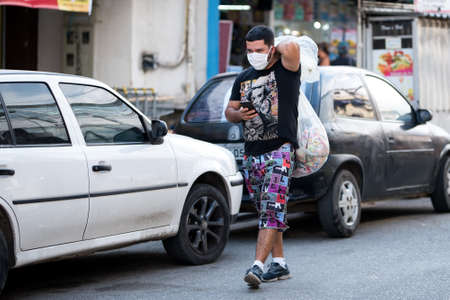 Rio de Janeiro, Brazil - July 3, 2020: People are wearing face masks during the Coronavirus pandemic in suburban area of the city. Man carrying big plastic bag on his back. Редакционное