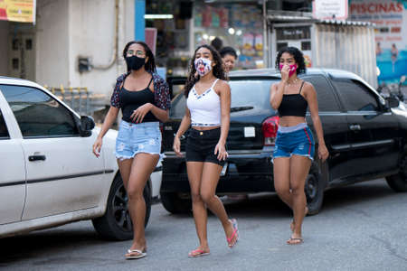Rio de Janeiro, Brazil - July 3, 2020: People are wearing face masks during the Coronavirus pandemic in suburban area of the city. Three young women walking down the street.
