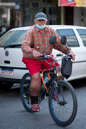 Rio de Janeiro, Brazil - July 3, 2020: People are wearing face masks during the Coronavirus pandemic in suburban area of the city. Elderly man with a cigarette on a bicycle. Редакционное