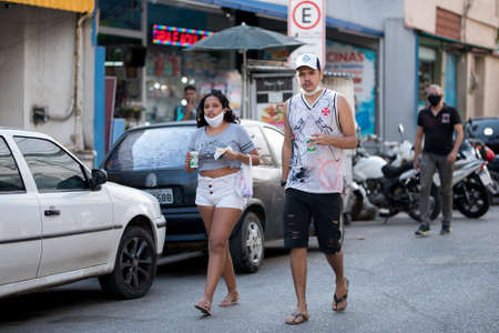 Rio de Janeiro, Brazil - July 3, 2020: People are wearing face masks during the Coronavirus pandemic in suburban area of the city. Man and woman walking while having a snack.