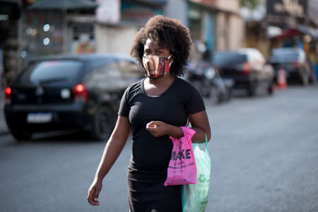 Rio de Janeiro, Brazil - July 3, 2020: People are wearing face masks during the Coronavirus pandemic in suburban area of the city. Woman carrying her bags on her hand.