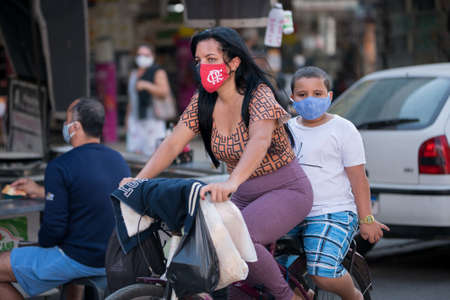 Rio de Janeiro, Brazil - July 3, 2020: People are wearing face masks during the Coronavirus pandemic in suburban area of the city. Woman on a bicycle with her son on a back. Редакционное