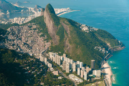 Aerial View of Two Brothers Mountain With Biggest in Brazil Favela Rocinha and Apartment Buildings at Bottom in Front of the Beach in Rio de Janeiro Фото со стока