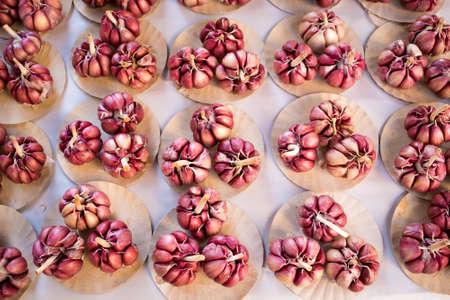 Fresh Violet Garlic Bulbs on Small Paper Plates at the Market Фото со стока - 154005687