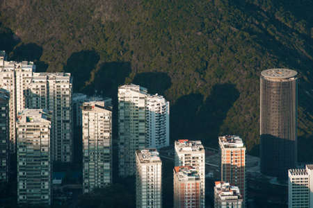 Aerial View of Apartment Buildings With Sunlight on Top of Them and a Hill Behind Фото со стока - 154020883