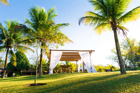 Beautiful Brazilian Style Outdoor Wedding Ceremony Set Up Between Palm Trees by Sunset Фото со стока - 155823714