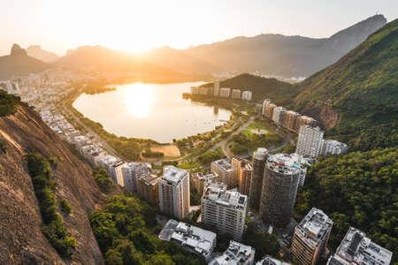 Beautiful View of Rodrigo de Freitas Lagoon by Sunset Surrounded by Apartment Buildings and Mountains in Rio de Janeiro, Brazil. Фото со стока - 156064483
