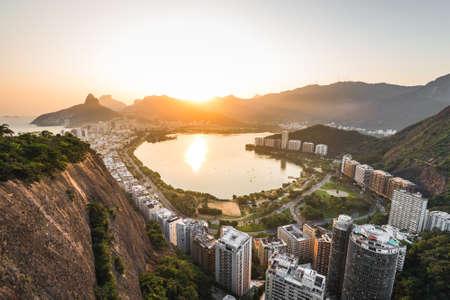 Beautiful View of Rodrigo de Freitas Lagoon by Sunset Surrounded by Apartment Buildings and Mountains in Rio de Janeiro, Brazil. Фото со стока