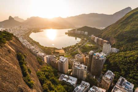 Beautiful View of Rodrigo de Freitas Lagoon by Sunset Surrounded by Apartment Buildings and Mountains in Rio de Janeiro, Brazil. Фото со стока - 156064637