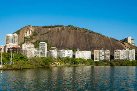 View of Mountains and Residential Buildings Around Rodrigo de Freitas Lagoon in Rio de Janeiro, Brazil. Фото со стока - 156054245