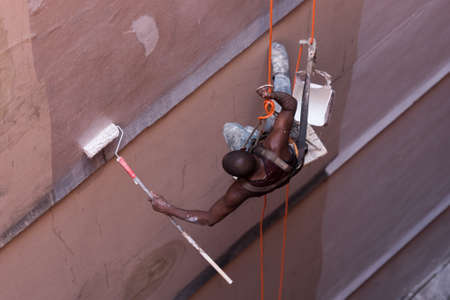 Painter Hanging on Rope and Painting a Building Wall