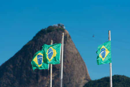 Three Waving Brazilian Flags in the Wind With the Sugarloaf Mountain in the Background, Rio de Janeiro, Brazil Фото со стока