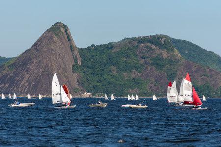 Rio de Janeiro, Brazil - December 4, 2020: A bunch of white sailboats riding in Guanabara bay with mountain landscape in the horizon. Редакционное
