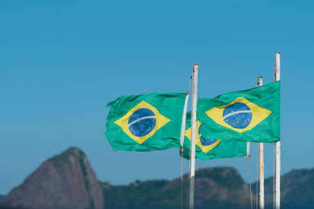 Three Waving Brazilian Flags in the Wind With Mountains in the Background, Rio de Janeiro, Brazil Фото со стока