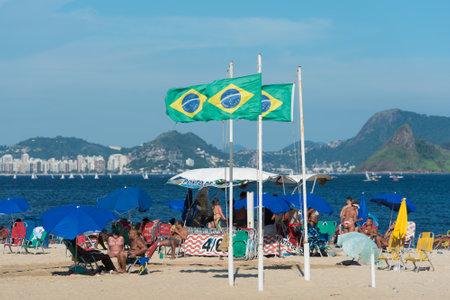 Rio de Janeiro, Brazil - December 4, 2020: Beach tent with three Brazilian flags at the Flamengo beach. Редакционное