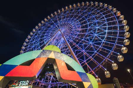 Rio de Janeiro, Brazil - January 4, 2021: Rio Star ferris wheel at night is illuminated with colorful RGB led lights. Редакционное