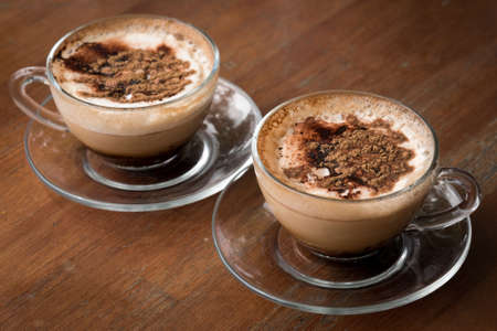 Two Glass Cups of Cappuccino Coffee on Wooden Table Фото со стока