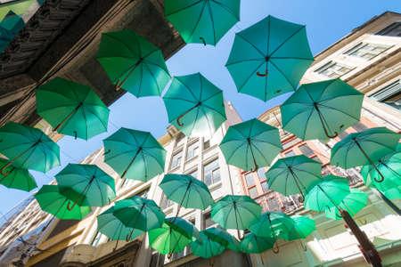 Decorative Green Umbrellas Hanging Between Buildings in the City