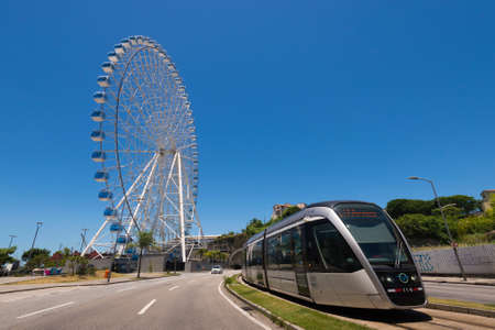 Rio de Janeiro, Brazil - January 18, 2021: Rio Star ferris wheel in revitalized part of the city and public tram VLT passing by.