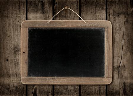 Blackboard on a old dark wood wall background texture Standard-Bild