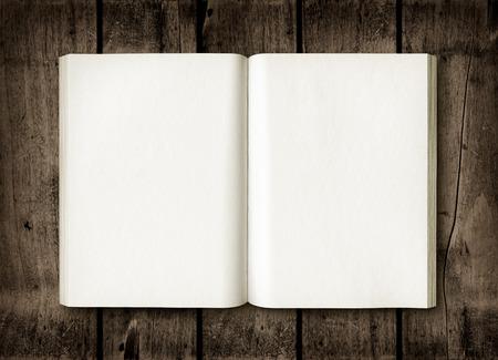 ダークウッドのテーブルに開いた本。モックアップ