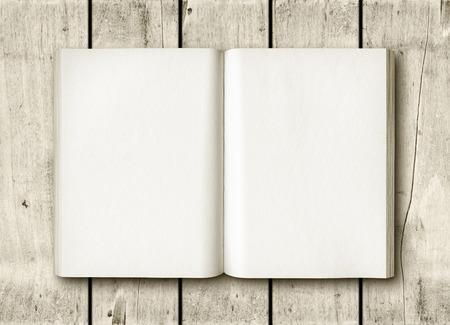 白い木のテーブルに開いた本。モックアップ 写真素材