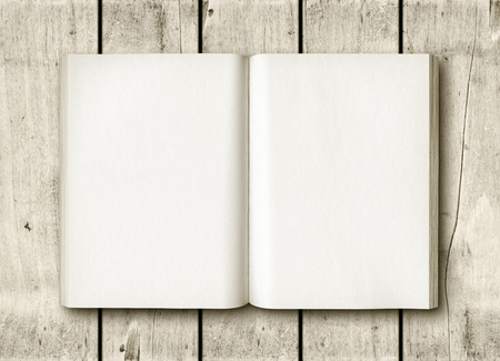 Open book on a white wood table. Mockup