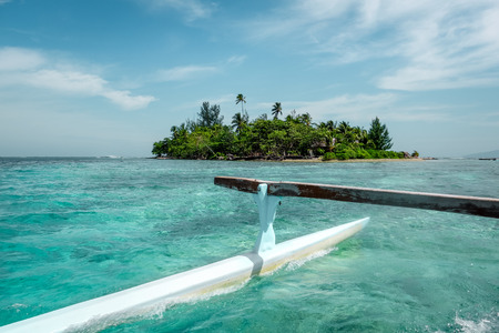 motu: Pirogue on the way to paradise tropical atoll in Moorea Island lagoon. French Polynesia Stock Photo