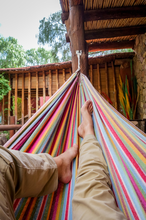 subjective: Man relaxing in a colored hammock. Subjective view