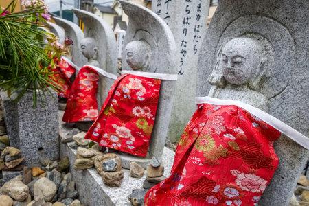Estatuas de Jizo con baberos rojos en el templo de Arashiyama, Kyoto, Japón Foto de archivo - 93245602
