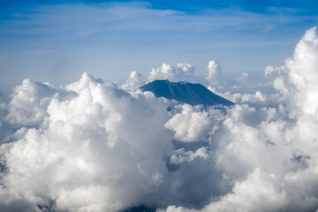 Airplane flying above clouds and Mount Agung volcano, Bali, Indonesia