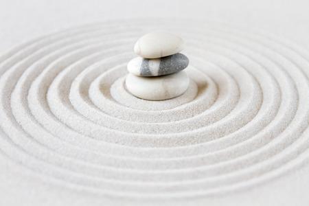 Czarno-białe kamienie na piasku. Zen japoński ogród w tle sceny