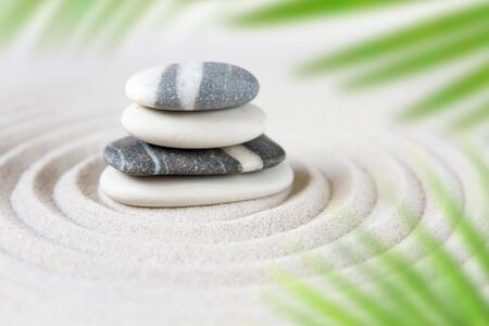 Stones pile in the sand behind palm leaves. Zen japanese garden