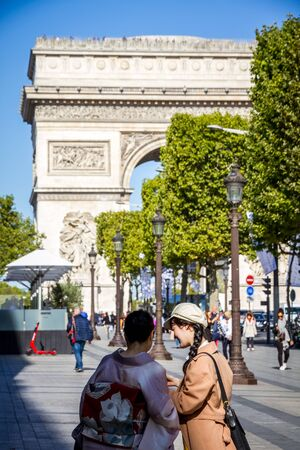 Paris/France - September 10, 2019 : Two Japanese tourist taking pictures in front of the Arc de Triomphe on Champs-Elysees avenue 報道画像
