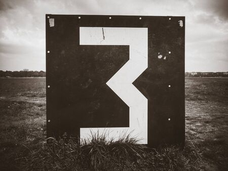 Number 3 countdown panel on Templehof Airport runway, Berlin, Germany. Black and white picture