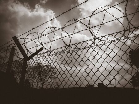 Barbed wire fence on a dramatic sky background. Black and white picture