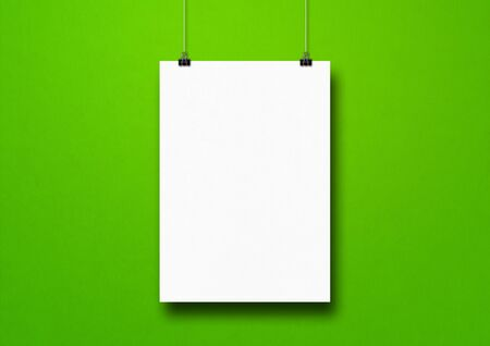 White poster hanging on a green wall with clips. Blank mockup template