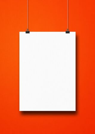 White poster hanging on a red wall with clips. Blank mockup template