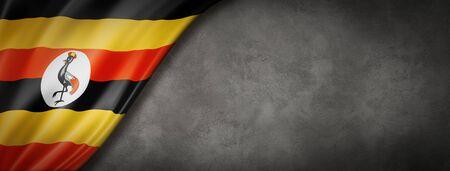 Uganda flag on concrete wall. Horizontal panoramic banner. 3D illustration