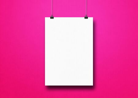 White poster hanging on a pink wall with clips. Blank mockup template