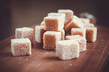 Brown cane sugar cubes on a wooden cutting board